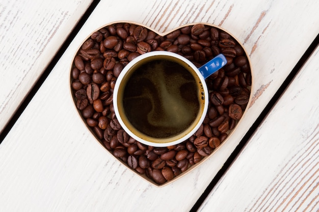Cup of coffee standing over heart made of coffee grains. coffee love concept. white wooden surface.