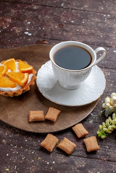Cup of coffee strong and hot along with cookies and orange cake on wooden desk, fruit bake cake coffee biscuit
