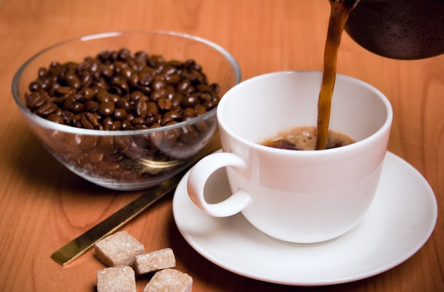 Cup of coffee, sugar and beans in glass bowl on wooden table