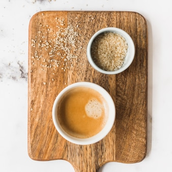 Cup of coffee and sugar on wooden chopping board