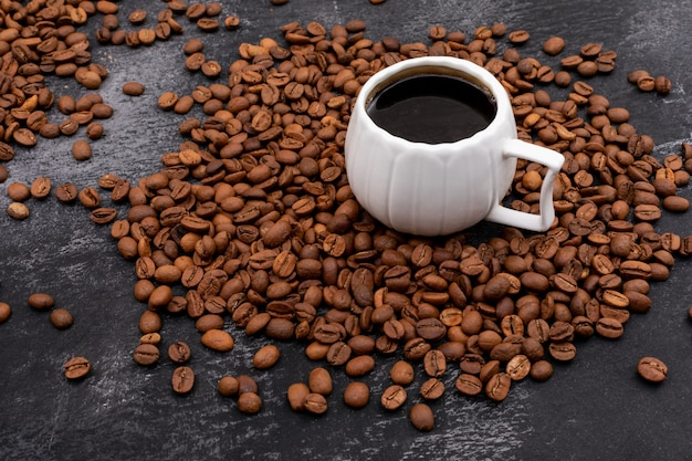 Cup of coffee surrounded with coffee beans on black surface