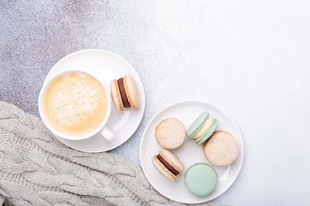 Cup of coffee, sweater and macarons on stone background. copy space. flat lay, top view - image