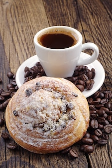 Cup of coffee, sweet bun and coffee beans on wooden table