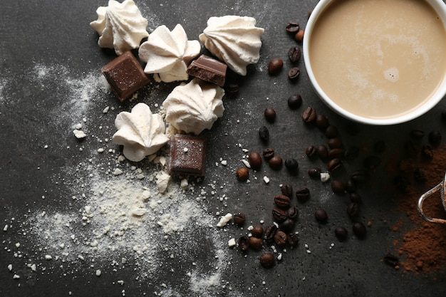 Cup of coffee and sweets on black wooden table