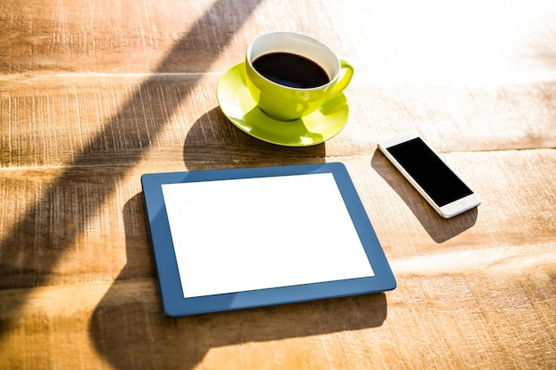 Cup of coffee and tablet pc on a desk