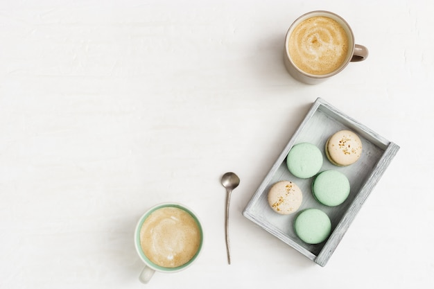 Cup coffee and tasty macaroons on light table with copy space. cappuccino and sweets in wooden box for relaxing. top view and flat lay.