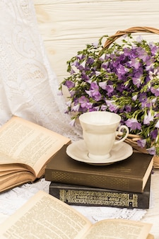 Cup coffee (tea), books and bouquet flax in wicker basket. retro style, vintage