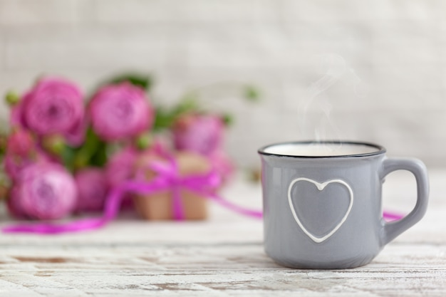Cup of coffee or tea with heart, present and roses copy space valentines day concept.