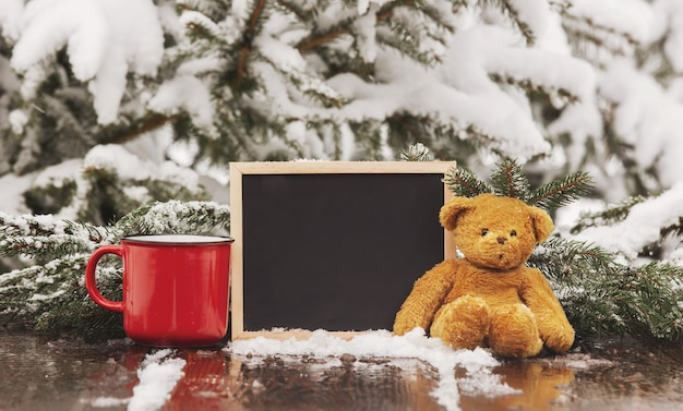 Cup of coffee, teddy bear and blackboard on wooden table in snow