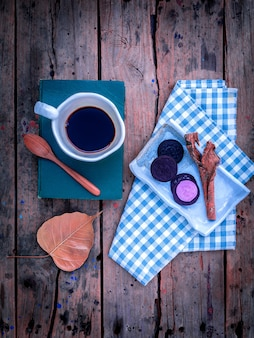 Cup of coffee  on textbook on rustic wooden table.