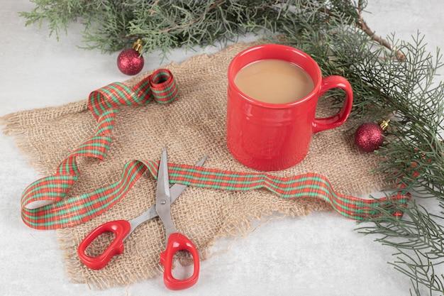 Tazza di caffè legata con il nastro sulla superficie bianca