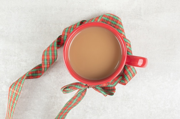 Cup of coffee tied with ribbon on white surface