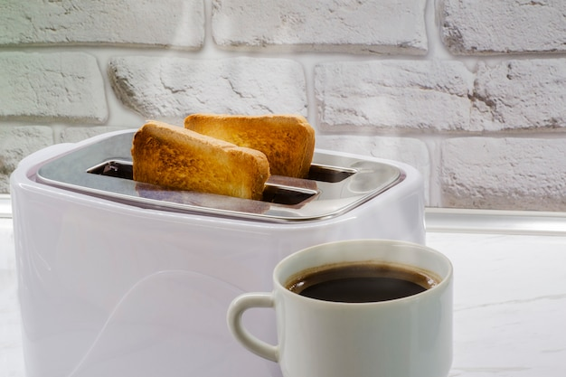 A cup of coffee and toast in a toaster