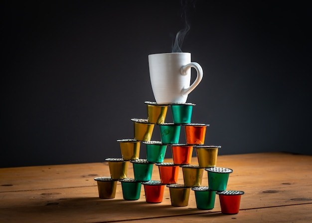 Cup of coffee on top of a tower made with colored coffee pods and used on wooden table