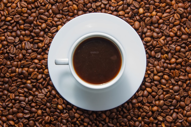 A cup of coffee top view with coffee beans on background