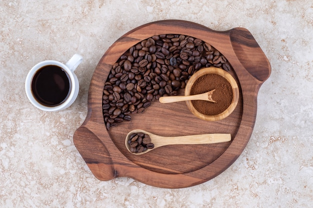 A cup of coffee next to a tray of coffee beans and ground coffee powder
