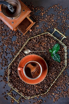 Cup of coffee on tray with coffee beans on black table background. |top view, close up.