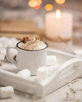 Cup of coffee on tray with marshmallows and candle