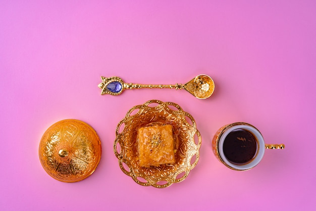 Cup of coffee and turkish dessert baklava on pink