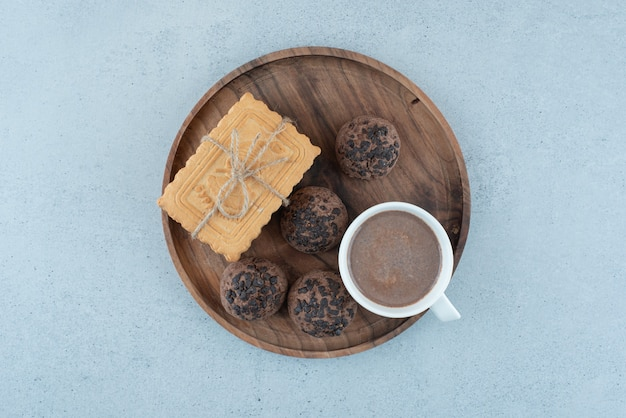 Cup of coffee and various cookies on wooden plate. high quality photo