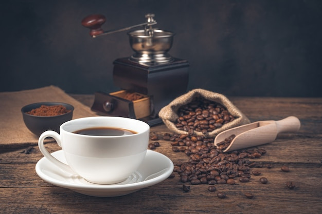 A cup of coffee on a vintage brown wall with a coffee grinder. side view, horizontal.
