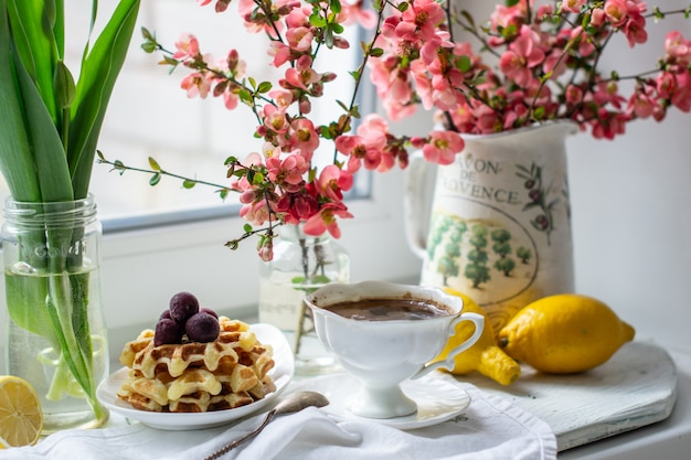 A cup of coffee and waffles with lemons