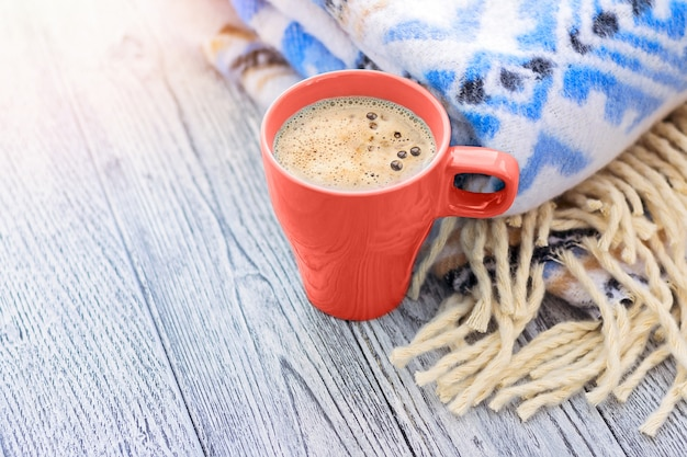 Cup of coffee and warm blanket with blue pattern on wooden table.