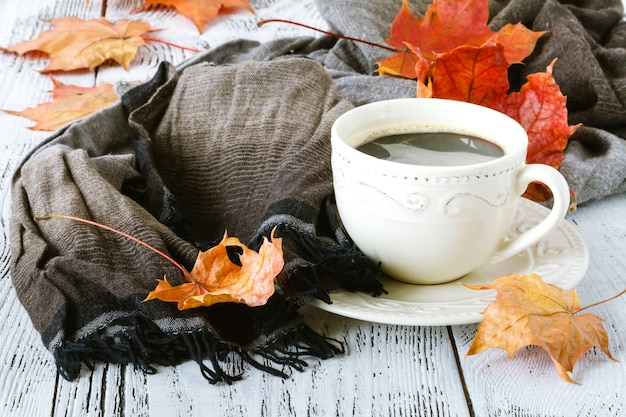 Cup of coffee and a warm scarf on wooden table surface