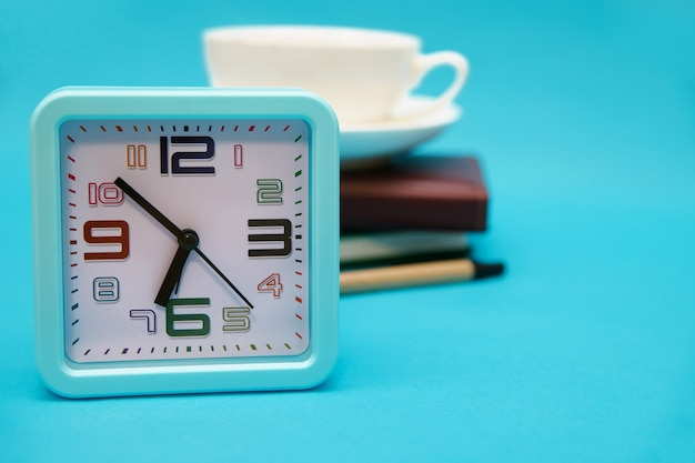 A cup of coffee, a watch, and a notebook on a blue background. the concept of the business theme. packing in the early morning. planning of work and recreation.
