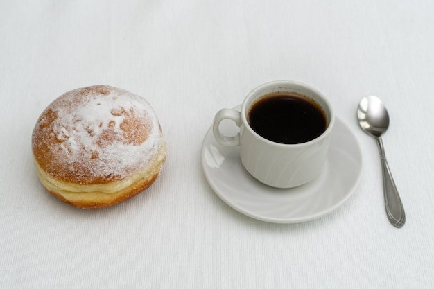 Cup of coffee in a white cup with a spoon and a donut on a light surface