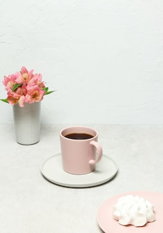 Cup of coffee, white marshmallow, flowers on grey stone table