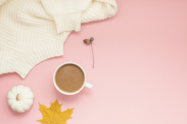 Cup of coffee and white sweater on pink
