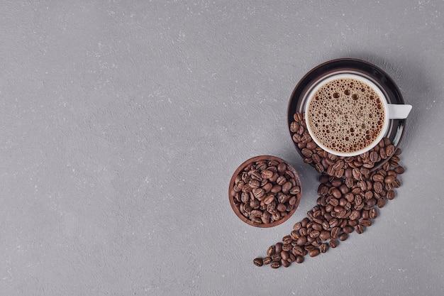 Una tazza di caffè con chicchi di arabica intorno, vista dall'alto.