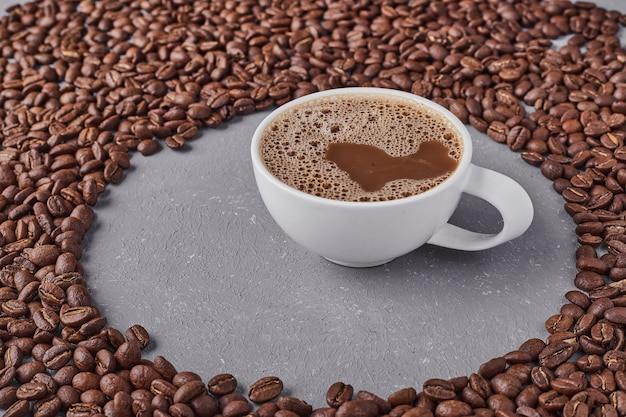 A cup of coffee with arabica beans around.