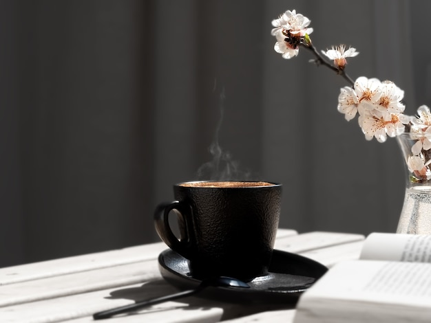 Cup of coffee with aromatic espresso on a wooden table, next to an open book and branch of blooming sakura