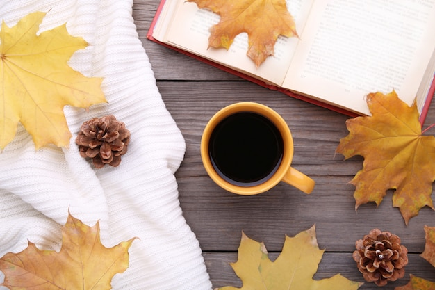 Cup of coffee with autumn leave and old book on wooden background
