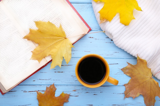 Cup of coffee with autumn leaves and old book on blue background