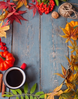 Cup of coffee with autumn leaves and small pumpkins