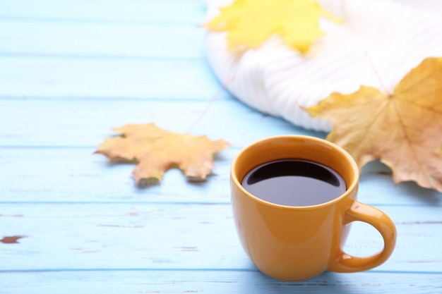 Cup of coffee with autumn leaves and sweater on wooden background