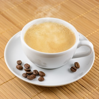 Cup of coffee with beans on bamboo matt background