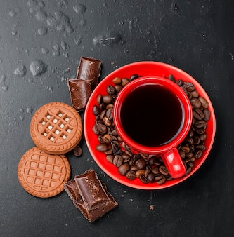 Cup of coffee with biscuits and chocolate on a black background