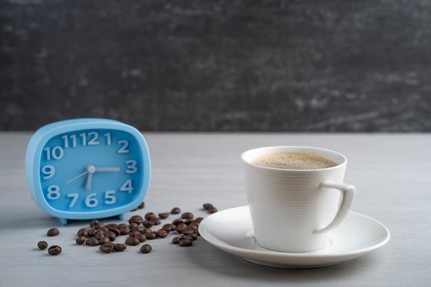 Чашка кофе с синим будильником.