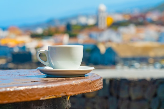 Cup of coffee with a blurred view of a garachico town on the ocean shore