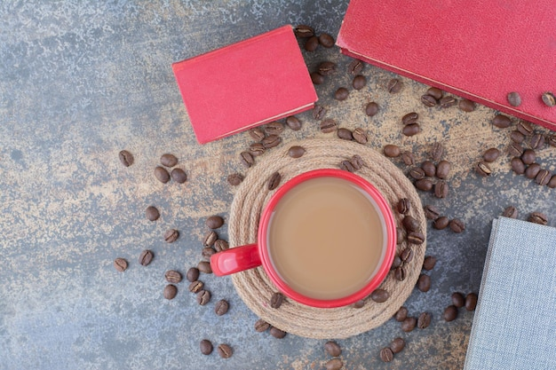 A cup of coffee with book and coffee beans on marble background. high quality photo