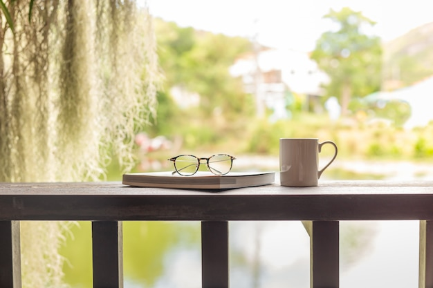 Cup of coffee with book and eye glasses on wooden top.