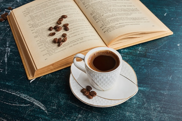 A cup of coffee with a book.