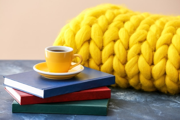 Cup of coffee with books and knitted plaid on table