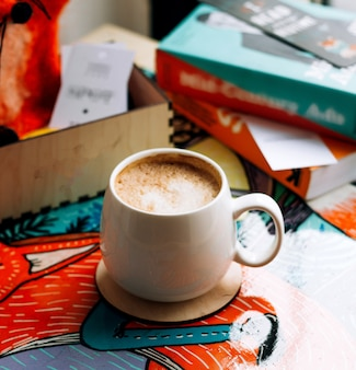 A cup of coffee with books on the table