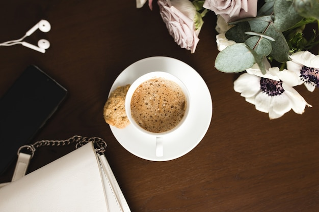 A cup of coffee with a bouquet of tender anemone, eucalyptus branches and pastel purple roses, a woman handbag, headphones and a phone on a brown wooden table.