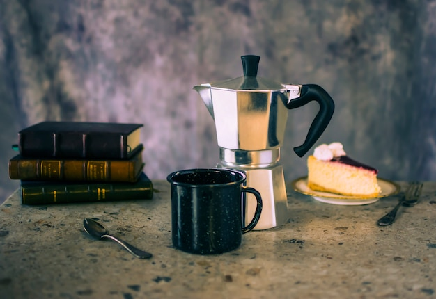 Cup of coffee with cake and books
